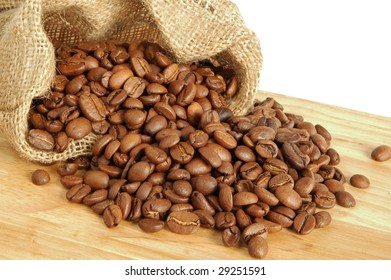 Coffee beans in canvas sack on wooden background