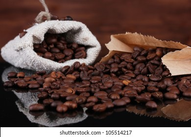 Coffee beans in canvas sack and paper bag isolated on wooden