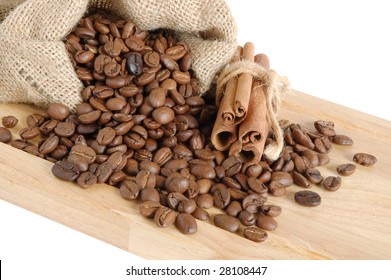 Coffee beans and cinnamon sticks in canvas sack on wooden background