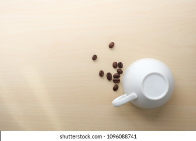 Coffee beans close to white inverted cup on wooden table with sunlight, no more coffee.
