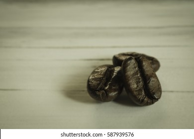 Coffee beans closeup on background white wooden.