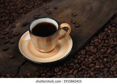 Coffee beans with colorful coffee cups on wood.