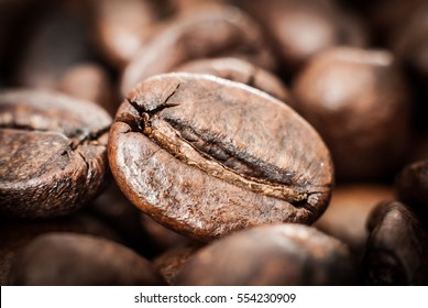 Coffee beans concept on wooden table background. Close up macro photography.