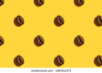 Coffee beans creative pattern on yellow background. Top view.