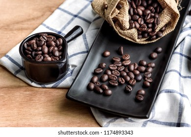 coffee beans in cup and bag on wooden background, selective focus