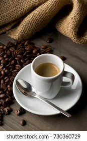 Coffee beans and cup of espresso on dark wooden table background
