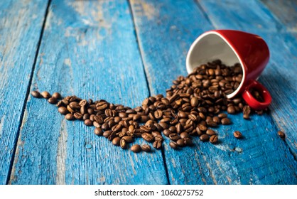 Coffee beans in coffee cup on old wooden painted in blue planks table