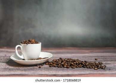 Coffee beans in a coffee cup on a wooden background.