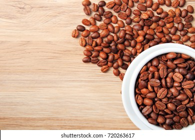 Coffee beans in coffee cup on wooden