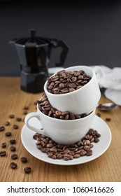 Coffee beans in the cup and coffee percolator on wooden table with black background