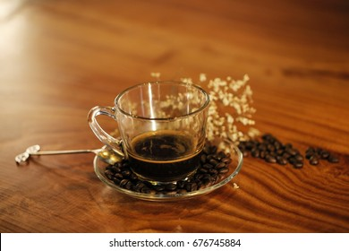 Coffee beans, a coffee cup, spoon on wooden table