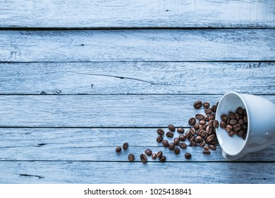 Coffee beans and coffee cups are placed on a white wooden floor.