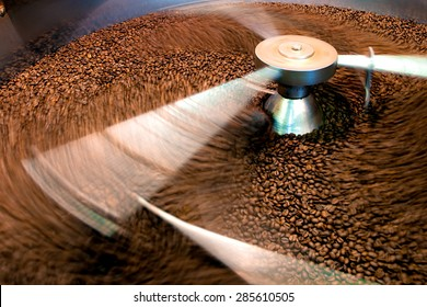 Coffee beans during the roasting process, moving paddle of the screening hopper cooling the coffee beans after roasting. Drum type roaster