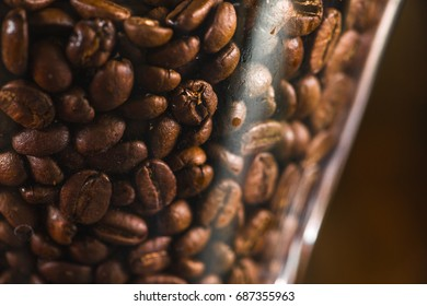 Coffee beans in espresso machine jar background close up