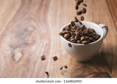 Coffee beans falling into coffee cup on wood table