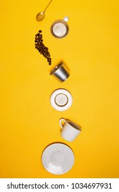 "Coffee beans ""falling"" into disassembled Vietnamese Phin filter from golden tea spoon in the white espresso cup with saucer. Flatlay, yellow background"