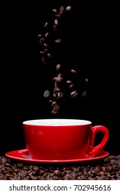 Coffee beans falling into red coffee cup.