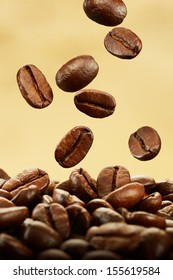 coffee beans falling on pile against brown background