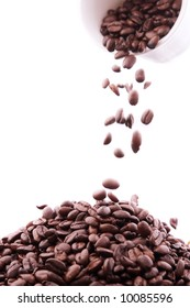 Coffee beans falling out of a white coffee cup on a pile of coffee beans.