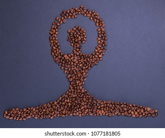coffee beans in the form of a balerine who sits in splits on grey mat surface and make hands up