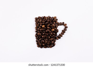 Coffee beans forming a mug on a white background