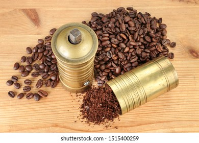 Coffee beans and fresh grounds in a brass coffee grinder