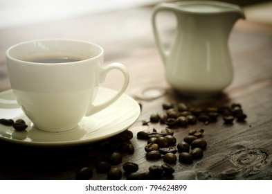 Coffee beans, glass and equipment for drinking coffee with warm light