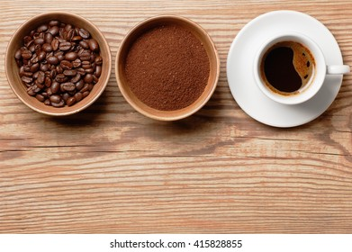 Coffee beans, ground coffee and cup of brewed coffee on rustic wooden table, view from above with space for text