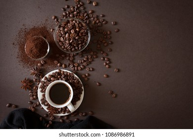 Coffee beans and ground powder on brown background. Top view with copy space for your tex