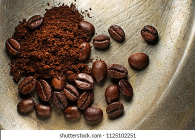 Coffee beans and ground powder on rustic plate background.