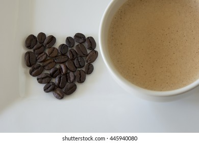 Coffee beans in a heart shape besides a cup of coffee