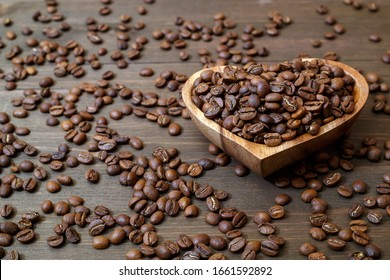 Coffee beans in a heart-shaped plate, coffee beans scattered on a wooden table