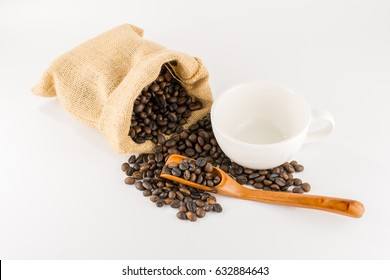 Coffee beans in hemp bag, wooden spoon and empty white cup isolated on white