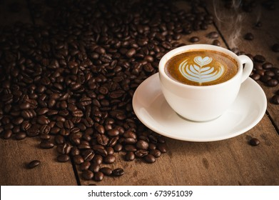 Coffee beans and Hot Cofee cup with latte art on wooden background. side view with copy space for your text