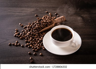 Coffee beans and hot coffee on the table - Shutterstock ID 1728806332