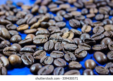Coffee beans isolated on blue wooden background