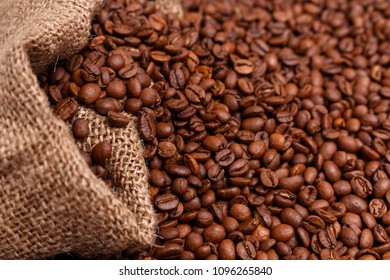 coffee beans in jute bag on wooden table. Burlap sack full of coffee beans on wood table