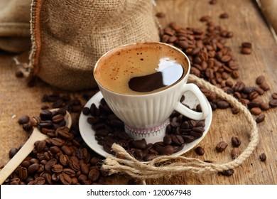 coffee beans in jute sack behind  cup of black coffee