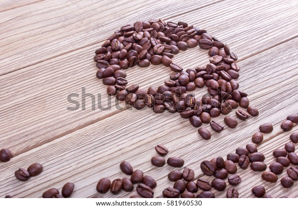 From coffee beans laid out a symbol of skull and bones. Coffee kills. Wooden background