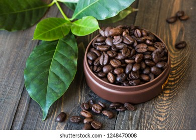 Coffee Beans and leaf over Wood Background