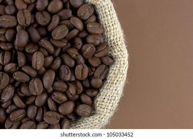 Coffee beans in a linen sack on brown background