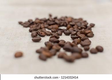 coffee beans lying on linnen white coffee bag