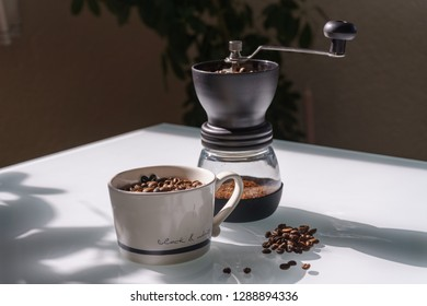 Coffee Beans in Mill and Mug on a Table