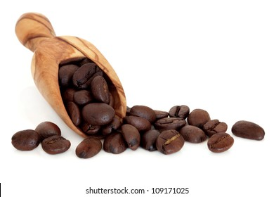 Coffee beans in an olive wood scoop over white background.