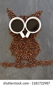 Coffee beans on a black background form the silhouette of an owl and two cups of coffee form their eyes - concept with coffee and night owls