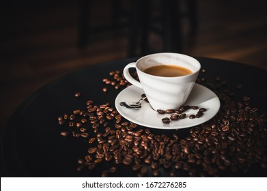 Coffee and coffee beans on black table.  Coffee beams closeup. Coffee theme. White cup on black table.