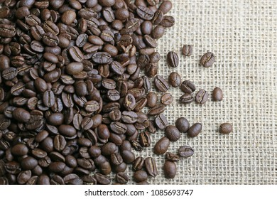 Coffee beans on brown jute texture.