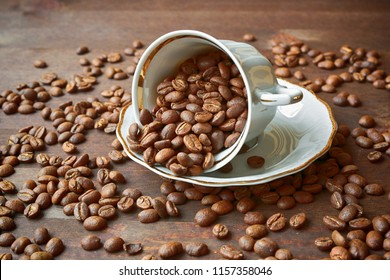 Coffee beans on the brown plate and in unturned porcelain cup