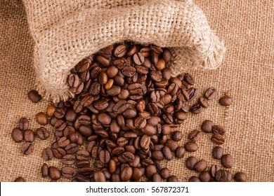 coffee beans on burlap background. roasted coffee beans isolated in white background. Roasted coffee beans background close up. Coffee beans pile from top on white background with copy space for text