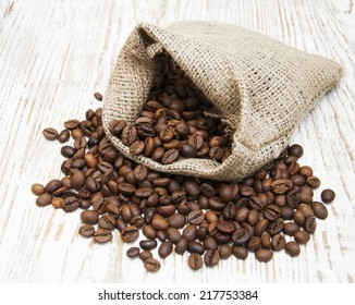 Coffee beans on burlap sack on a wooden background
